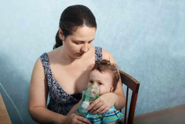Домашняя обстановка. Мама держит на руках ребенка, который сидит в маске. Малышу делают ингаляцию