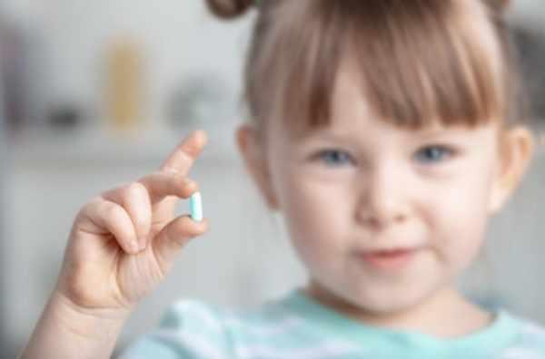 Девочка держит капсулу в руке