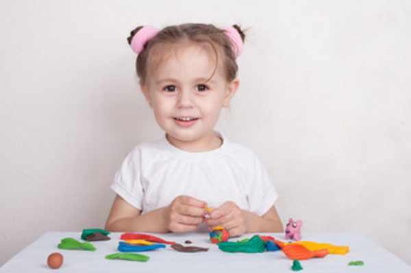 Маленькая девочка сидит за столом, собирается лепить