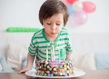 Ребенок задувает четыре свечи на торте