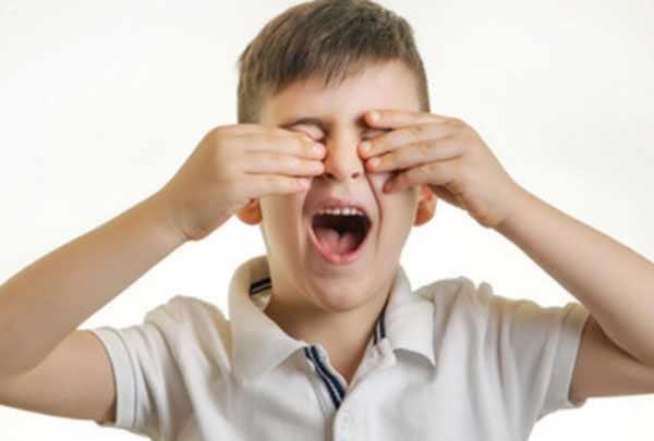 Мальчик трет глаза. Видно, что они у него болят