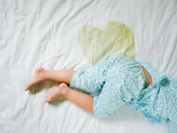 Ребенок лежит в постели, простынь записянная