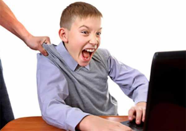 Мальчика пытаются оттянуть от компьютера. Он кричит и сопротивляется