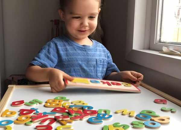 Девочка занимается изучением английского алфавита. Работает с деревянными буквами