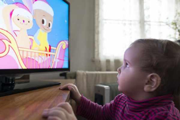 Маленькая девочка стоит возле экрана и смотрит мультик