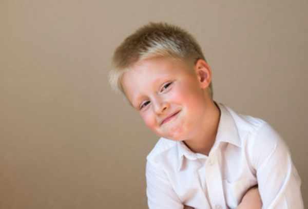 Мальчик со скрытой улыбкой, прячет руки под мышками