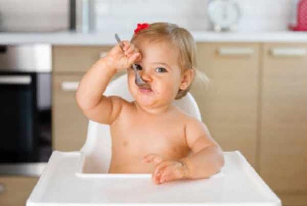 Маленькая девочка что-то ест с ложечки