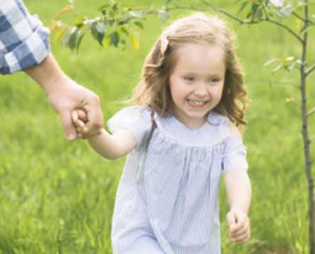 Девочка идет, держась за папину руку, и улыбается