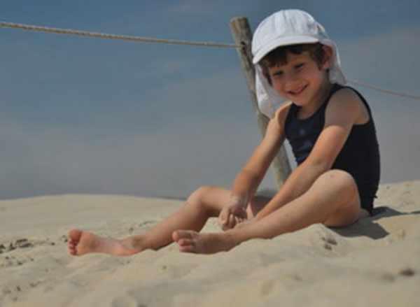 Мальчик в панамке сидит на песке