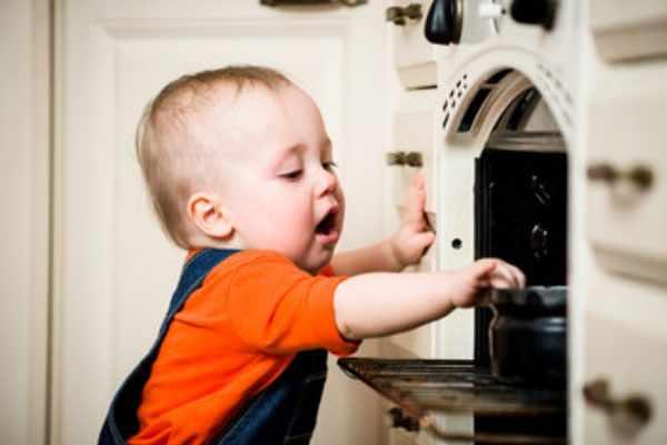 Ребенок дотрагивается до казанка , который стоит в духовке