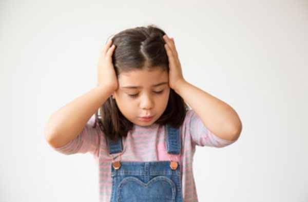Девочка держится за голову