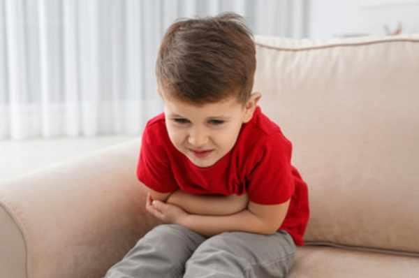 Мальчик сидит на диване и держится за живот