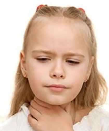 Девочка держится рукой за горло, которое болит