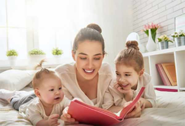 Мама читает книгу вместе с дочками