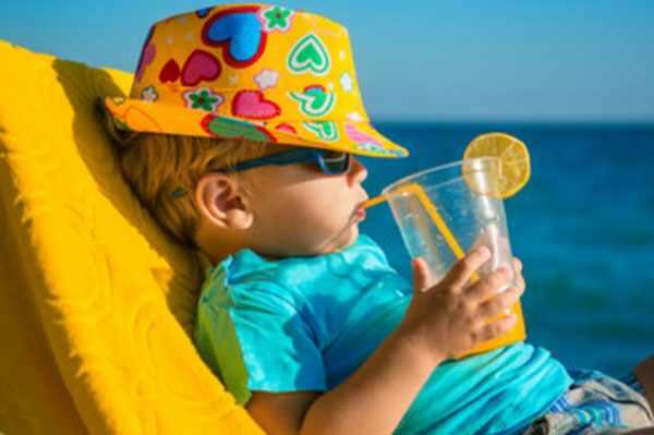 Мальчик в панамке со стаканом сока в руках лежит на кушетке