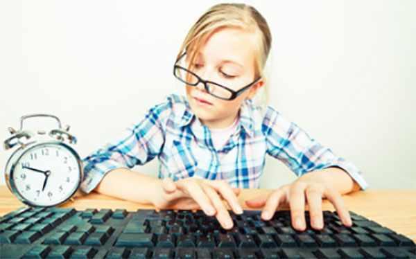Девочка печатает на клавиатуре и смотрит на часы