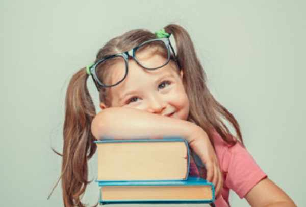 Девочка сидит возле стопки книг