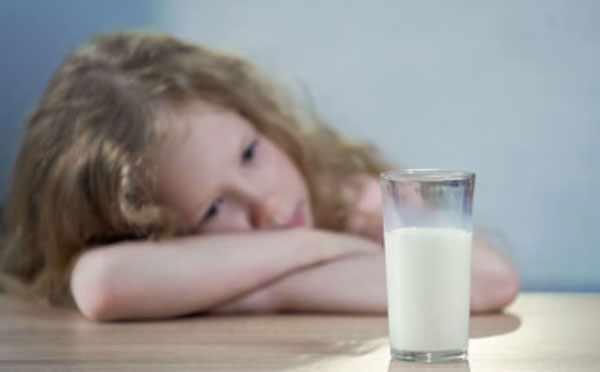 Грустная девочка смотрит на стакан с молоком