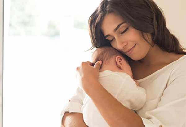 Мама прижимает новорожденного к себе