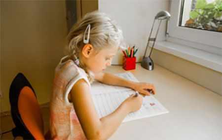 Девочка правильно сидит за столом и делает письменные уроки