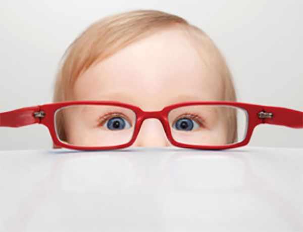 Маленький ребенок смотрит через очки, которые лежат на столе