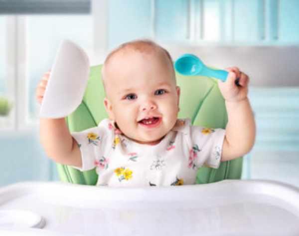 Ребенок держит тарелку и ложку. Он счастлив