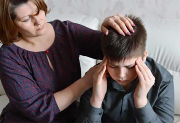 Мальчик держится за голову. Рядом сидит мама
