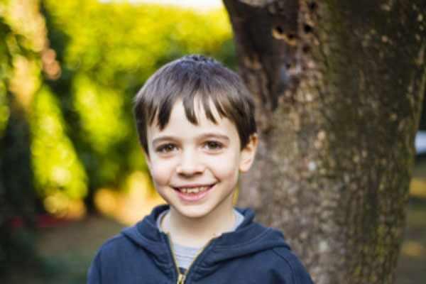 Улыбающийся мальчик стоит возле дерева