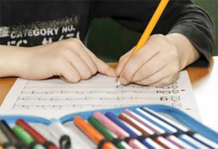 Ребенок заполняет прописи левой рукой