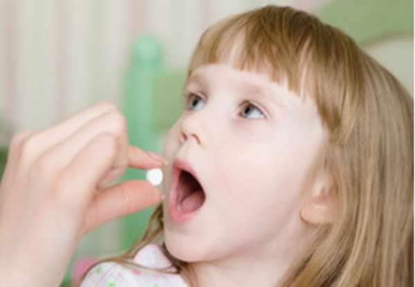 Мама кладет девочке в рот таблетку