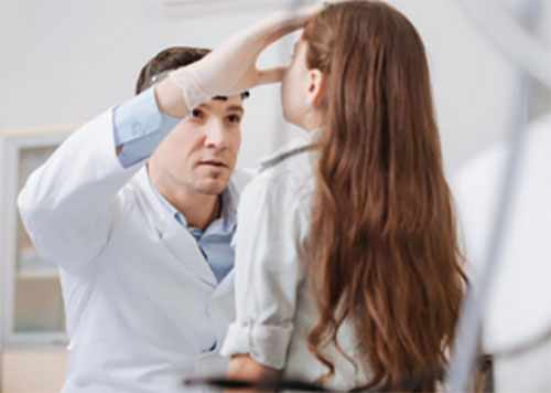Врач осматривает нос девочки
