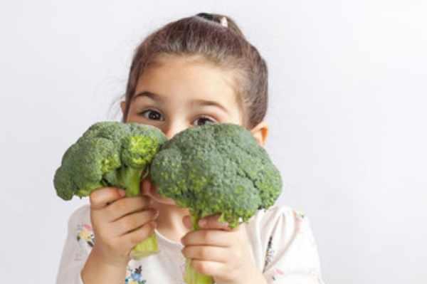 Девочка держит брокколи в руках