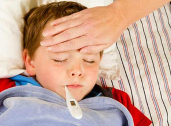 Больной мальчик лежит в постеле с градусником во рту. Мама трогает его лобик