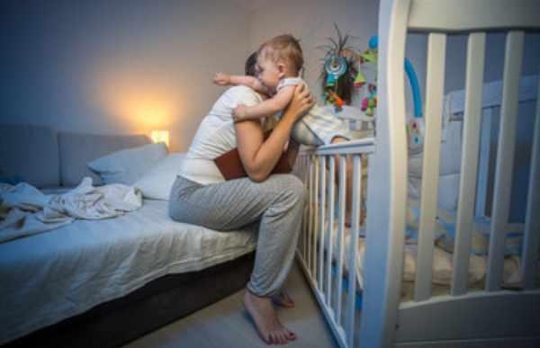 Мама достает ребенка из кроватки