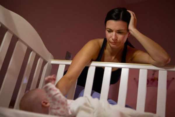 Мама ночью сидит возле кроватки ребенка. Она очень устала