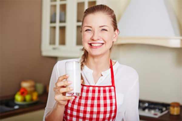 Женщина в фартуке со стаканом кефира в руке и следом от него над верхней губой