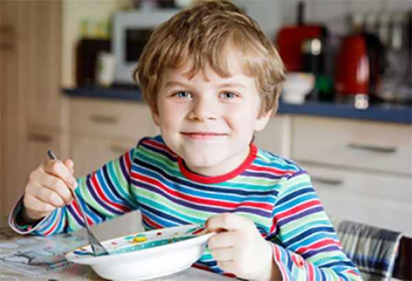 Ребенок улыбается и доедает суп