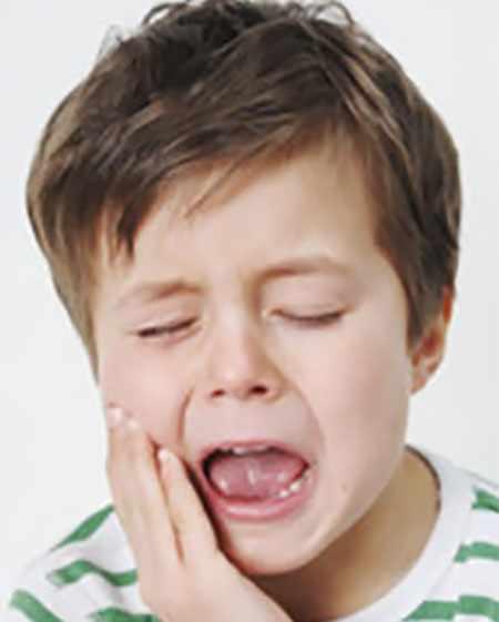 Мальчик держится рукой за щеку, ему явно больно