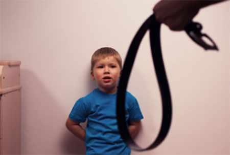 Мальчик стоит возле стены. К нему приближается взрослый с ремнем в руке