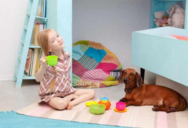 Девочка сидит на полу и играет со своей собакой