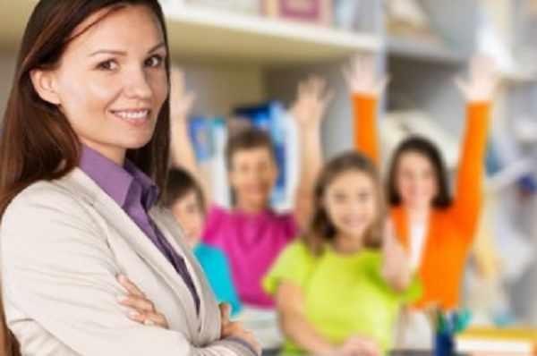 На переднем плане улыбается учительница. На заднем - счастливые дети