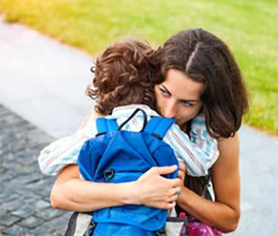 Мама обнимает своего маленького ученика
