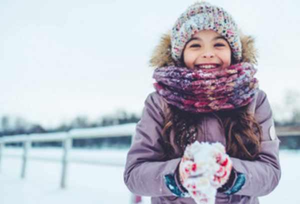 Девочка на улице зимой. В руках у нее снег