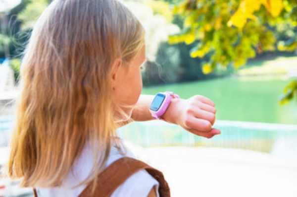 Девочка смотрит на свои смарт-часы, надетые ей на руку