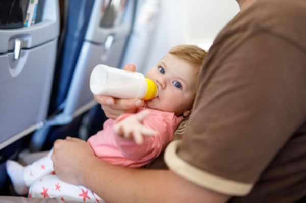 Ребенок сидит на руках родителя и пьет с бутылочки молоко