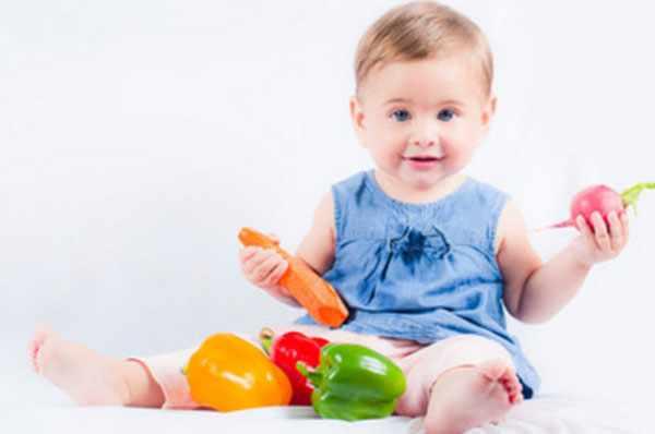 Маленькая девочка сидит. Перед ней лежат три болгарских перца. В руке морковь и редис