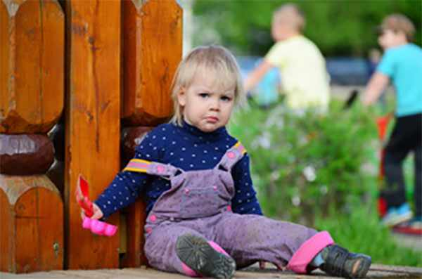 Двухлетняя девочка сидит на земле