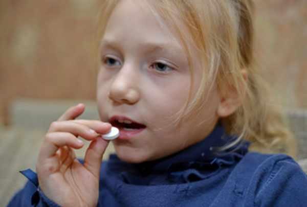 Девочка кладет таблетку в рот