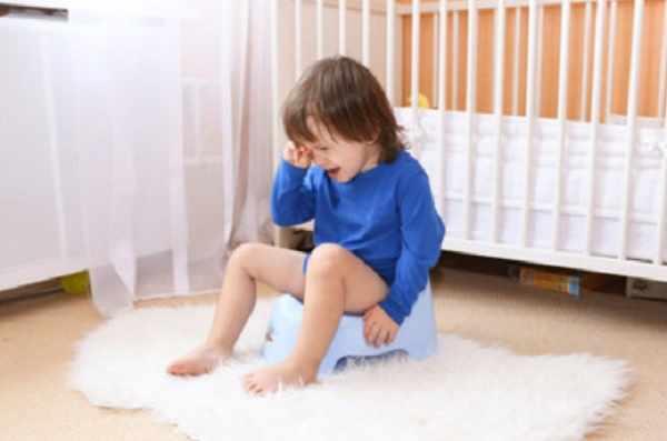 Ребенок плачет, сидя на горшочке