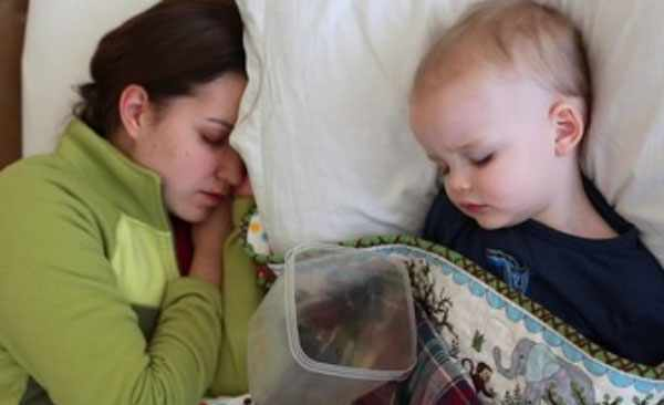 Мама спит рядом с ребенком. Возле малыша лежит емкость для возможной рвоты